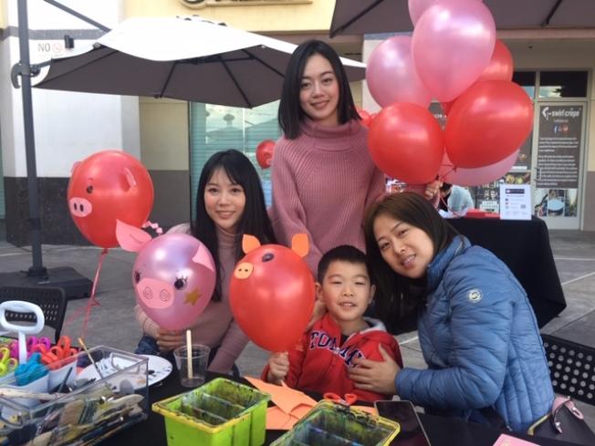 名画创意美术学院现场教孩子们美化气球,家长也饶有兴趣加入制作,倍加温馨。(记者杨青/摄影)
