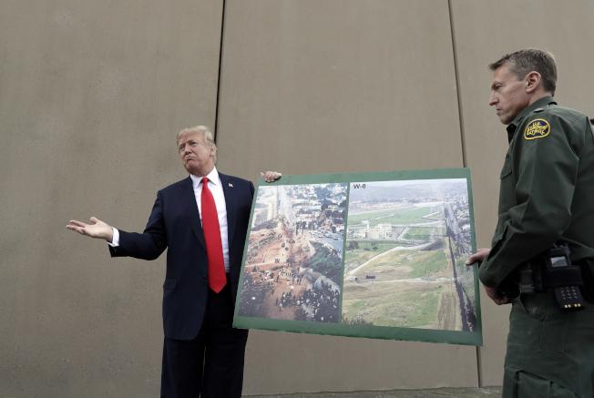 川普總統去年3月赴加州聖地牙哥推動興建邊牆,手拿美墨邊界照片。(美聯社)