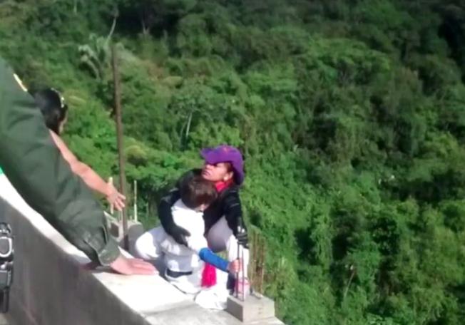 哥倫比亞一名單親媽媽克魯茲,因遭債主趕出家門、走投無路,在6日抱著10歲兒子跳橋輕生,在跳橋前,她的兒子還曾緊抓橋上欄杆,哭求媽媽不要跳;當局目前正持續調查這起案件,並查自殺及謀殺案的方向偵辦。圖片擷取Facebook/Ondas de Ibague影片