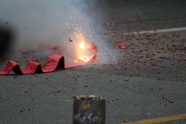 包瑟與高碩泰夫婦在遊行結尾一同點燃鞭炮,迎接中國新年。(記者張筠 / 攝影)
