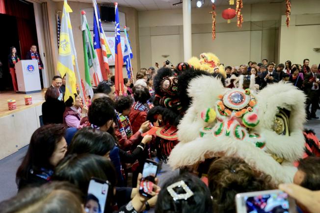 「洛杉磯各界新春聯歡團拜」吸引大量僑民參與。圖為僑民爭相向舞獅送紅包。(記者陳開/攝影)