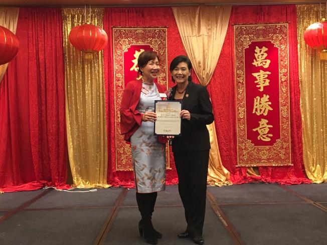 美中家長親子教育協會主席許偉文(左)從趙美心手中接過榮譽狀。(記者張宏/攝影)
