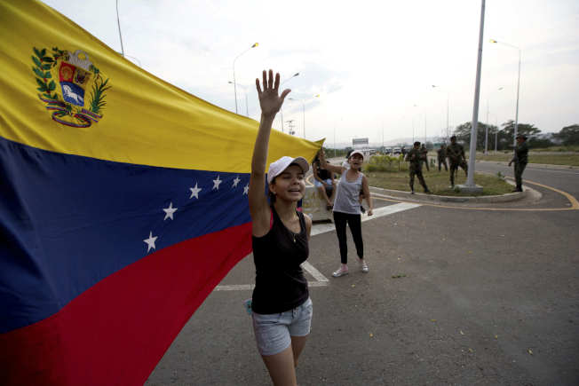委內瑞拉一名女子高喊「歡迎人道援助」,她的背後是委國國旗。(美聯社)
