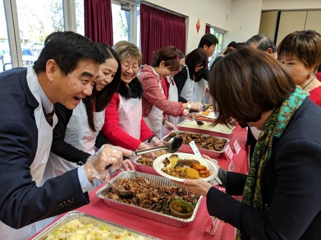 當日由僑務委員、僑領、經文處同仁幫參加的僑胞打菜。(記者李榮/攝影)