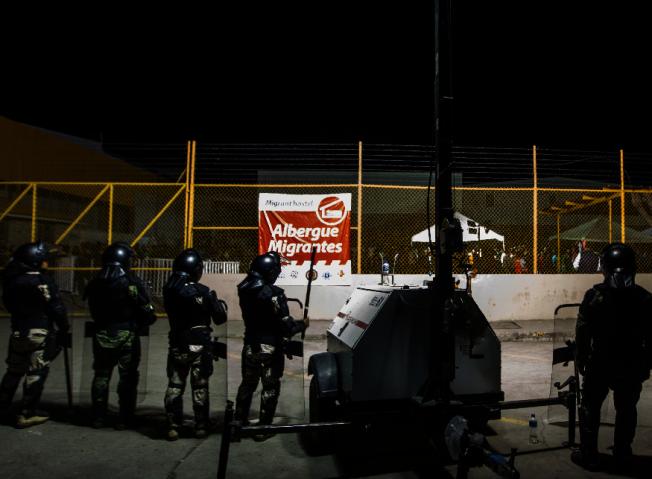 報導指出,新一批大篷車隊無證移民已抵達美墨邊界,都表示要進入美國。圖為墨國軍警在提璜納嚴陣以待。川普總統誓言要築牆來阻擋無證移民。(Getty Images)