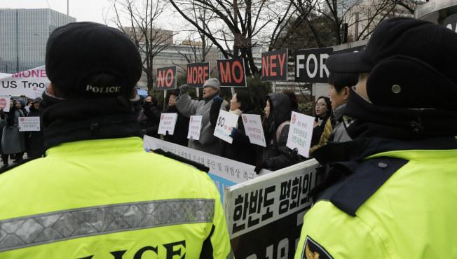 南韓民眾十日在南韓外交部附近示威,抗議政府屈從美方要求負擔更多駐韓美軍費用,員警在旁警戒。(美聯社)