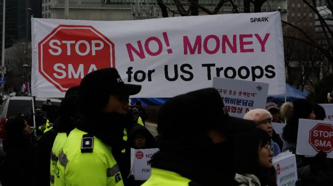 南韓民眾10日在南韓外交部附近示威,「不付錢,不准駐軍」,抗議政府屈從美方要求負擔更多駐韓美軍費用,員警在旁警戒。(美聯社)