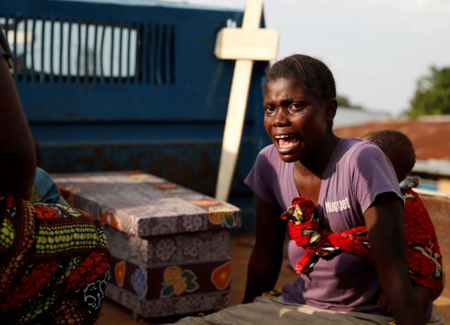 在剛果北基伍省的貝尼城,一名女子在疑似感染伊波拉而死亡的孩子棺木旁哭泣。(路透)