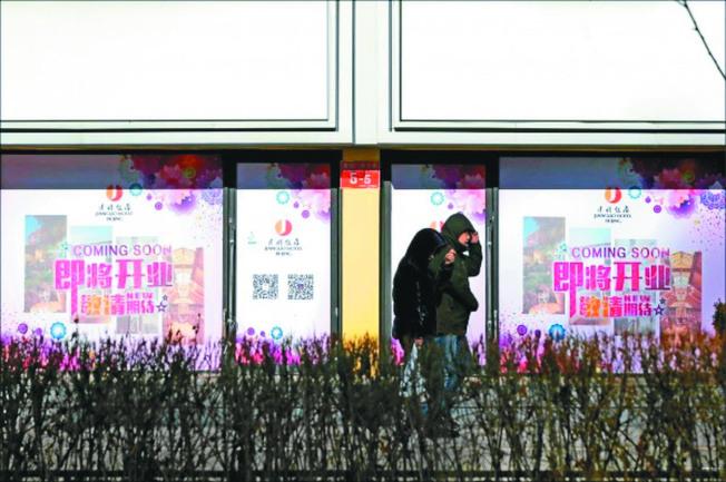 中國經濟成長出現減速現象,首季增速可能下滑到6%。圖為北京市民經過零售商店。(美聯社)