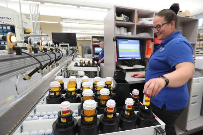 猶他州的藥廠工人正在包裝藥品。持有紅藍卡的病人對處方藥的價格過高無可奈何。(Getty Images)