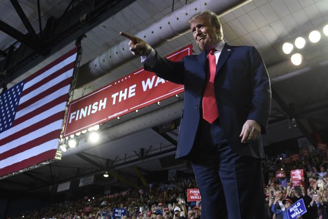 川普總統11日晚飛抵德州邊界城市艾爾巴索,出席當地支持民眾的大會。會場上布置了巨大標語「築完邊牆」。  (美聯社)