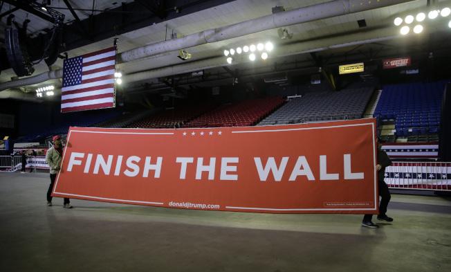 川普總統11日晚飛抵德州邊界城市艾爾巴索,出席當地支持民眾的大會。會場上布置了巨大標語「築完邊牆」。(美聯社)