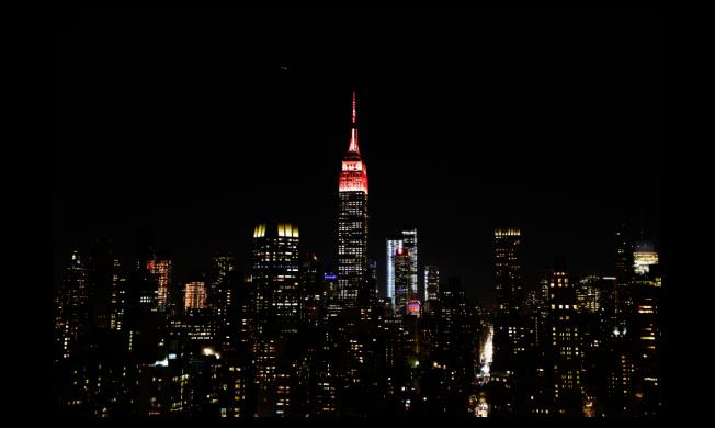 今年春節期間,大陸一對夫妻到紐約旅遊,卻因兩人激烈爭吵,導致丈夫遭美國警方逮捕。圖為除夕當晚,紐約帝國大廈為慶祝農曆新年而亮燈。(中新社)