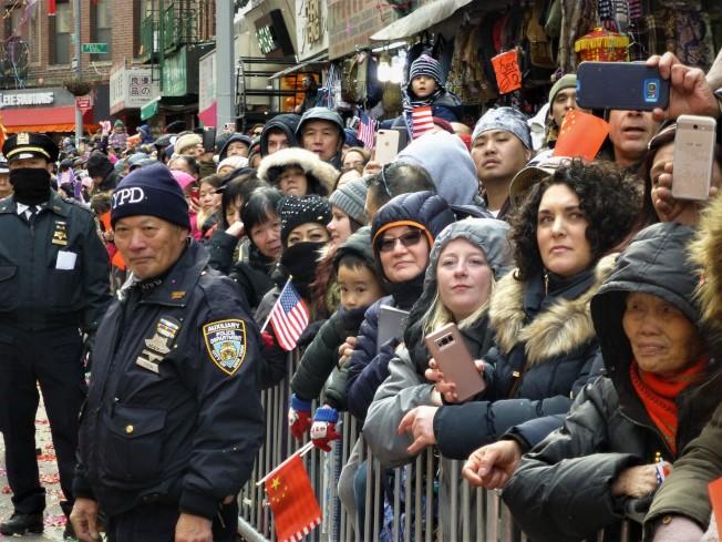 維持遊行秩序的華裔警員,與擠在欄邊翹首圍觀遊行隊伍的大批群眾。(記者張宗智/攝影)