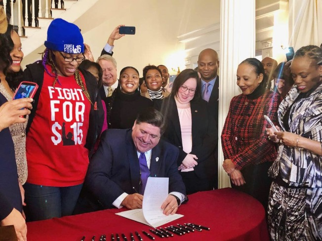 伊利諾州州長普立茲克(坐者)19日簽署通過最低時薪15元法案。(普立茲克臉書)