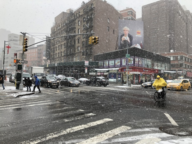 曼哈頓華埠堅尼路可看到外賣郎穿著雨衣冒雪送餐。(記者顏嘉瑩/攝影)