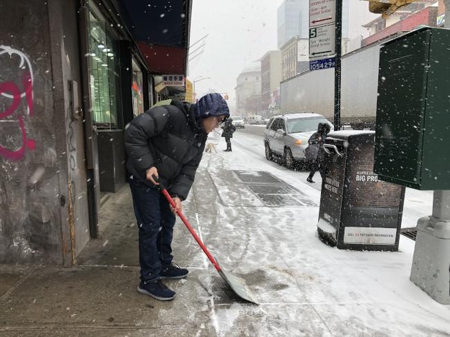 店家拿著雪鏟,鏟除門口的積雪。(記者顏嘉瑩/攝影)