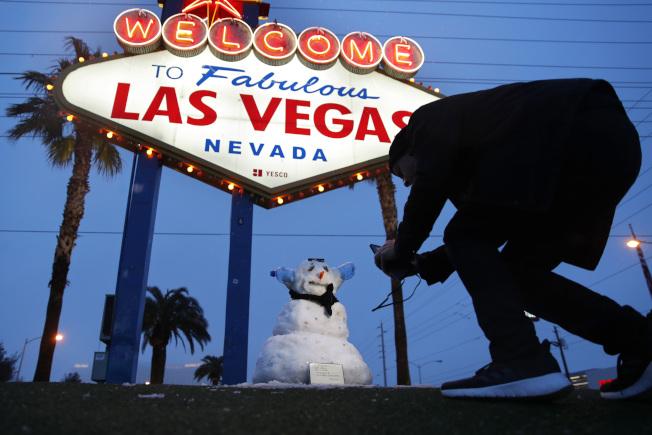 屬於沙漠氣候的賭城拉斯維加斯21日也下了雪,遊客甚至堆了雪人。(美聯社)