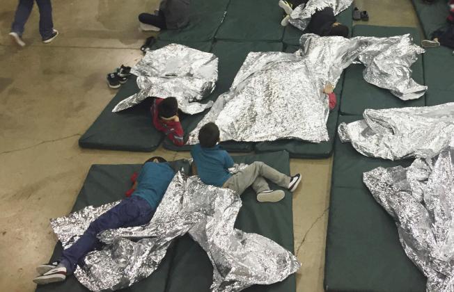 跨越德州南部邊界的無證移民被邊界巡邏探員逮捕後,關進拘留中心,青少年和兒童也和成人關押在一起。。(美聯社)