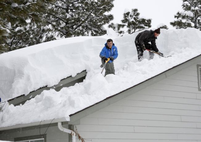 亞利桑納州旗杆市降雪超過40吋,宣布進入緊急狀態;居民們忙著清理屋頂的積雪,以免發生意外。(美聯社)