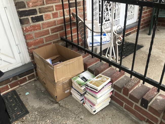 一名亞裔女子因吸食大麻及飲酒,23日下午1時挂坐在其三樓住所外沒有任何防護措施的窗戶外,被警方拉回屋內;圖為該女子住所門前放置的韓國書籍。(記者牟蘭/攝影)