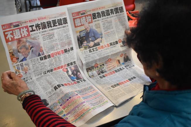 紐約華埠一位年長者在老人中心閱讀「世界日報」的專題報導。(記者顏嘉瑩/攝影)