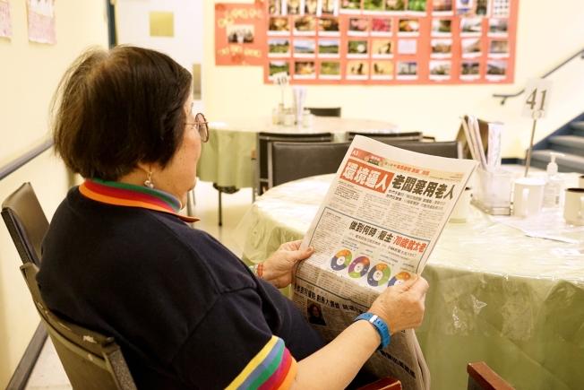 「世界日報」的「我不老,我工作」專題報導引起許多華裔的興趣。圖為華府一位年長者在老人中心閱讀報導。(圖由美京華人活動中心歡樂日間保健中心活動組提供)