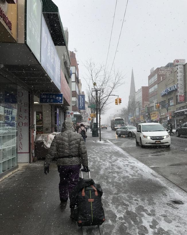 法拉盛街頭飄雪,民眾包裹嚴實行路匆匆。(記者劉大琪/攝影)