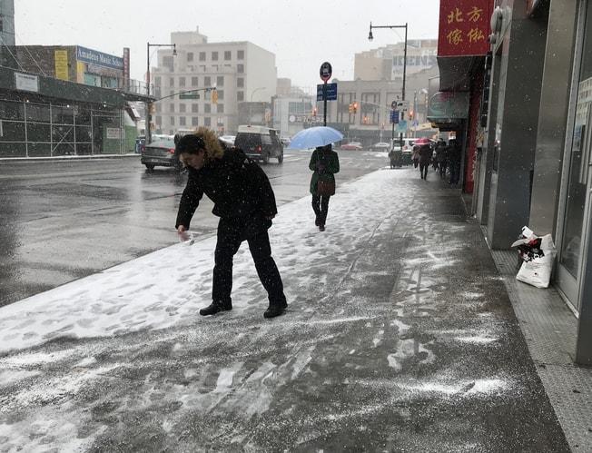 法拉盛街頭飄雪,商家忙著撒雪鹽。(記者劉大琪/攝影)