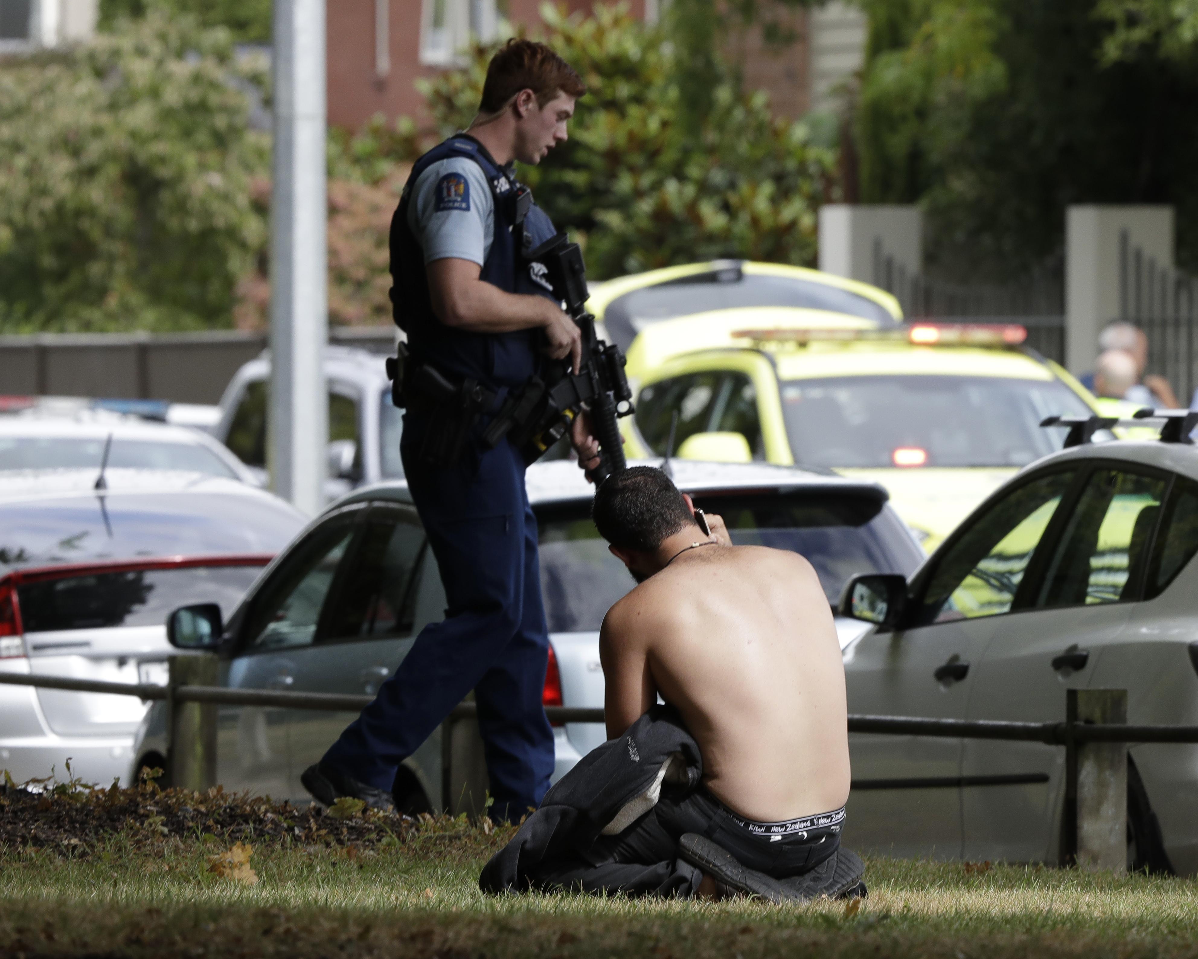 一名男子光著上身跪坐在草地上。(美聯社)