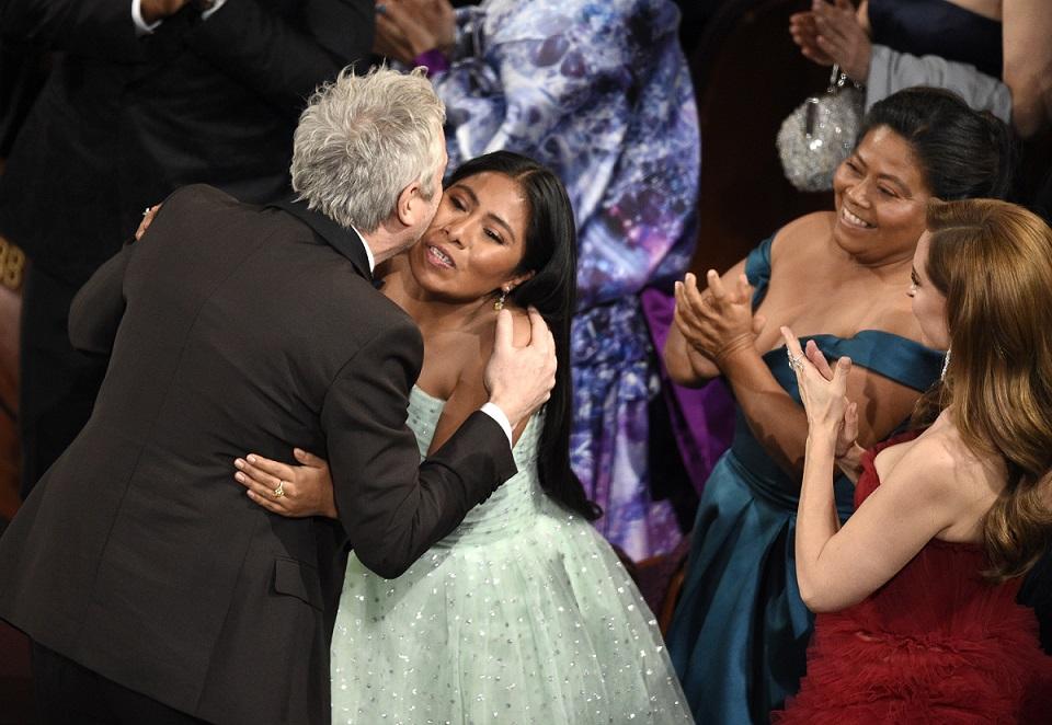《羅馬》主角亞莉札‧阿帕里希歐(Yalitza Aparicio,中)在導演艾方索柯朗(Alfonso Cuaron,左)獲得奧斯卡最佳攝影獎時向他祝賀。(美聯社)