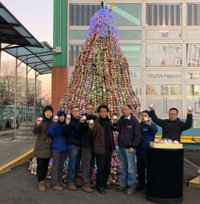 「希望之樹」在紐約皇后區白石鎮協和門窗廣場點燈,創作者林世寶(右四)和志工。(許振輝/攝影)