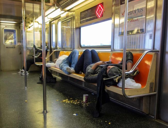 因為睡眠不足,有人甚至在地鐵車廂裡睡覺。(Getty Images)