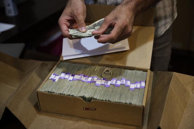 美國部分州因經濟好轉,財務改善,利用降稅率等方式回饋全州居民。圖為洛杉磯一家藥用大麻店東主,點數現金準備交稅。(美聯社)
