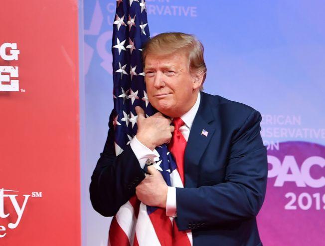 川普總統出席保守派政治行動大會,上台擁抱美國國旗。(Getty Images)