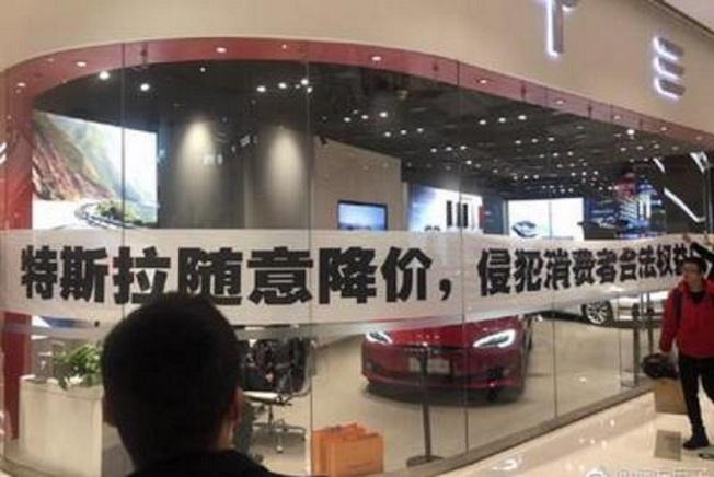 中國車主拉起「特斯拉隨意降價,侵犯消費者合法權益」的橫幅抗議。圖/新浪科技
