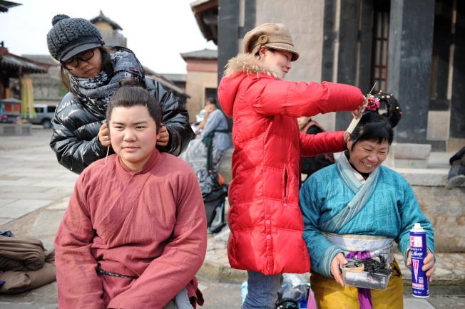 横店影视城里,化妆师为群众演员化妆。(新华社资料照片)