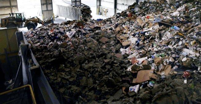 卡車將美國民眾未分類的回收物載到處理場,裡面有紙類、瓶館等。(美聯社)