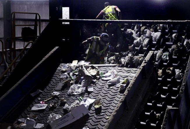 回收場員工必須把塑膠購物袋從機器中除掉,以免塑膠袋纏住機器。(美聯社)