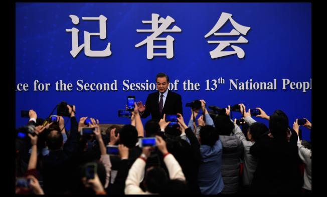 中國國務委員兼外交部長王毅8日上午記者會結束後準備離開時,現場媒體頻頻追問與台灣相關的問題。(新華社)