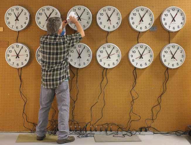今年美國日光節約時間從10日凌晨2時開始,圖為麻州著名的Wegman鐘表廠工作人員正在擦拭時鐘。(美聯社)