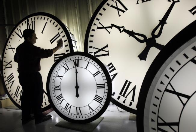 今年美國日光節約時間從10日凌晨2時開始,圖為麻州著名的Wegman鐘表廠工作人員正在擦拭大鐘。(美聯社)