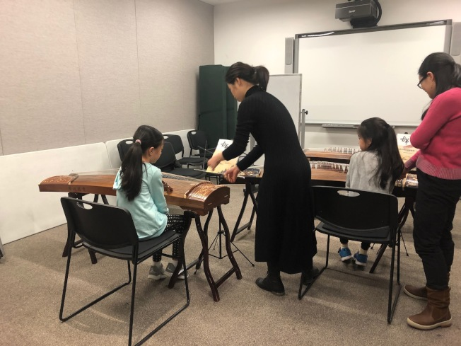 老师向在场学生们演示古筝演奏。(记者和钊宇/摄影)