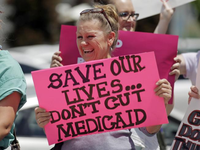 川普總統11日提交2020會計年度聯邦總預算案,其中大力增加軍費,但刪減包括白卡Medicaid在內的福利支出,勢將招到國會反對。 圖為猶他州一名婦女手持反對削減Medicaid的抗議標語。(美聯社)