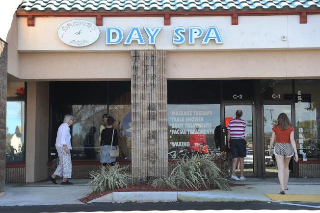 「亞洲蘭花日間水療店」被關後,好奇的民眾在店外窺視。(Getty Images)