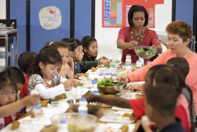 紐約市公校下學期將跟隨多個城市的腳步,實施「周一無肉日」。圖為長期推動學童健康食物的前第一夫人米雪兒.歐巴馬2010年5月在新罕布夏州一所小學和學童們吃午餐。(Getty Images)