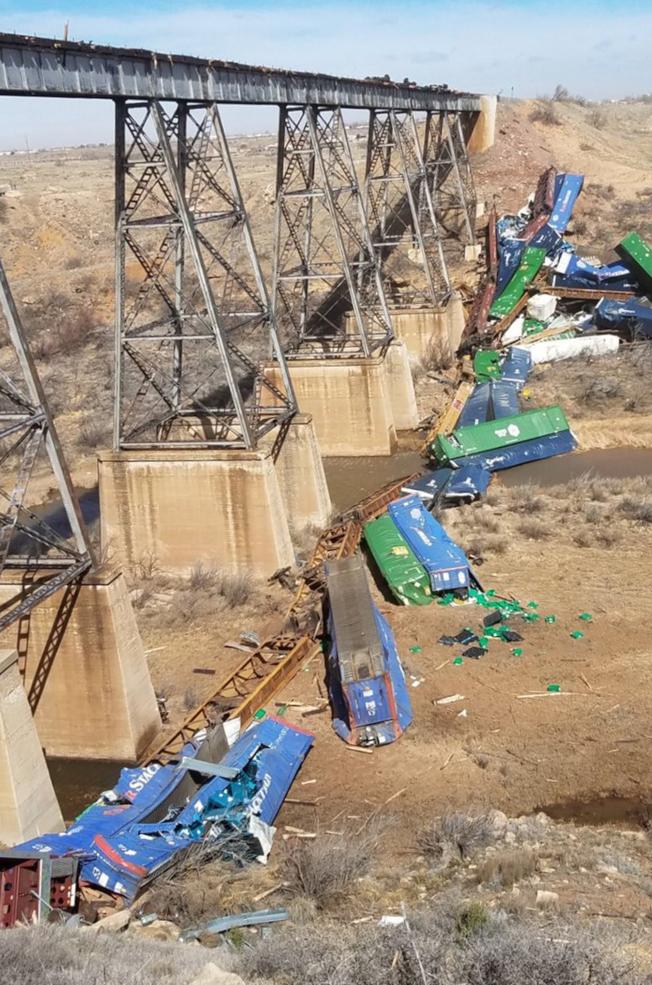 大平原區和中西部地區13日遭歷史性「炸彈氣旋」肆虐,引發廣大地區出現時速超過70哩的強風。圖為新墨西哥州東部有一列貨運火車被強風從橋上吹落至乾涸河床上。(美聯社)