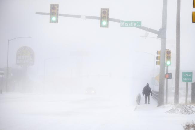懷俄明州13日大雪,一名夏艷市(Cheyenne)居民在茫茫大雪中步行回家。(美聯社)