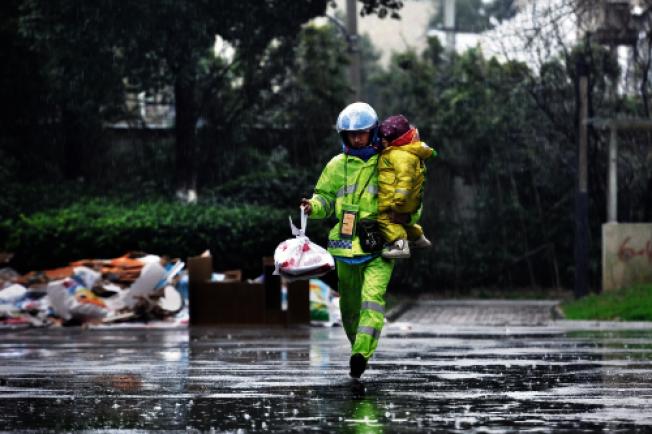 雨中,李帮勇抱著不到三岁的女儿送外卖。(取材自南湖晚报)