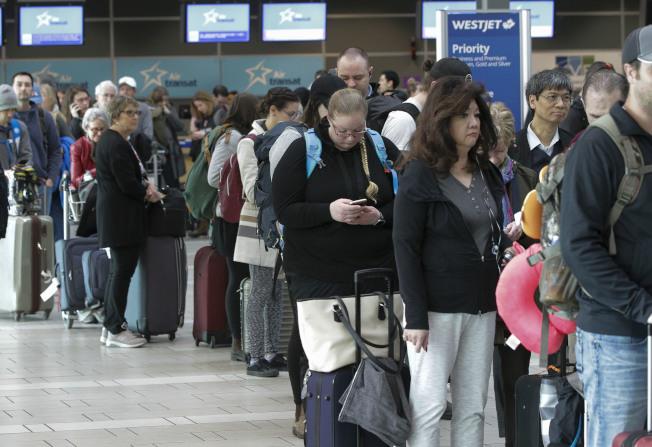 加拿大宣布全面禁飛波音737 Max 8飛機,圖為旅客在溫哥華機場出境大廳大排長龍。(新華社)